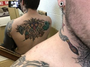 Hard to get a shot of, in progress Majora's Mask back piece. Originally drew it myself, with some minor changes added from the artist afterwards. Done by Matt at Sovereign Arms Tattoo Co. in Grand Rapids.