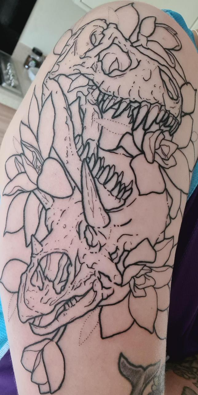 Line work completed on my upper arm piece. Dino skulls with magnolia star wars done at Holey Skin in Bristol by Nate Roberts