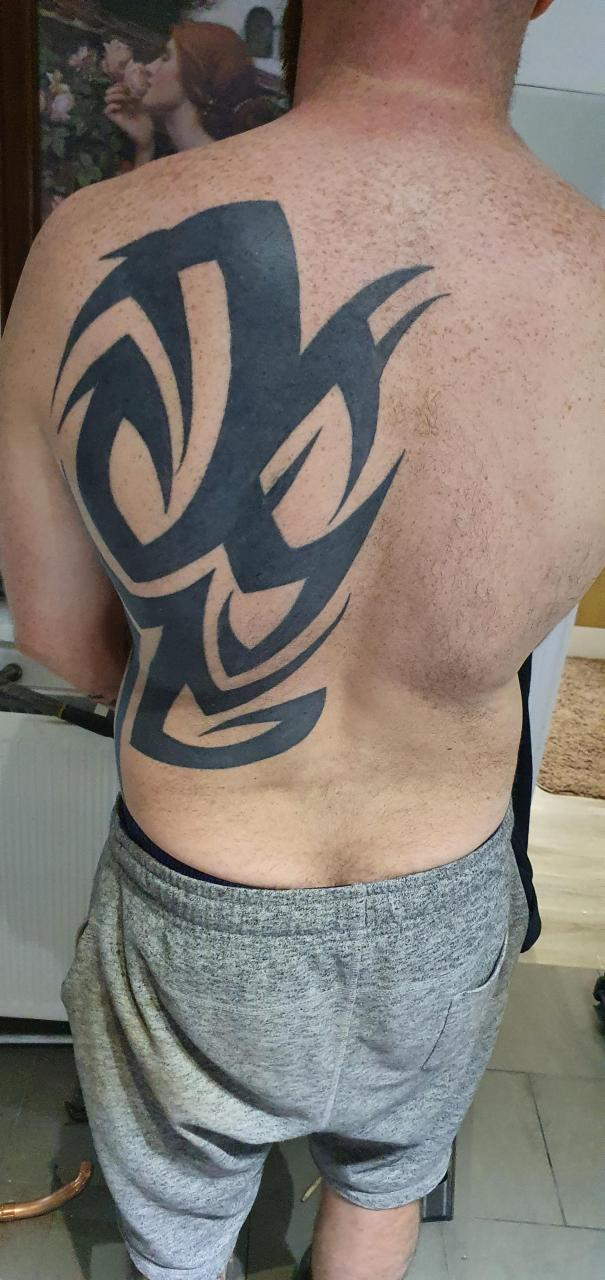 My friend got this back piece when he was younger and hates it. He wants to somehow integrate it into a bigger back piece that hides the original. Can somebody help out with some design ideas please 😊